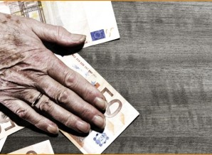 Hand of elderly woman on table with euro